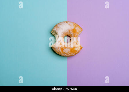 Köstliche Krapfen, von zwei Standorten gebissen, blau und violett gefärbten Hintergrund. Flach Bild - Stockfoto