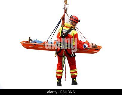 Hoher winkel Retter abseilen, während die Rettung einer Person in einer Rettung Korb, einem professionellen Feuerwehrmann der Berufsfeuerwehr - Stockfoto
