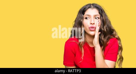 Junge schöne Frau legere t-shirt Hand auf Mund, geheime Gerücht, Flüstern bösartige talk Gespräch - Stockfoto