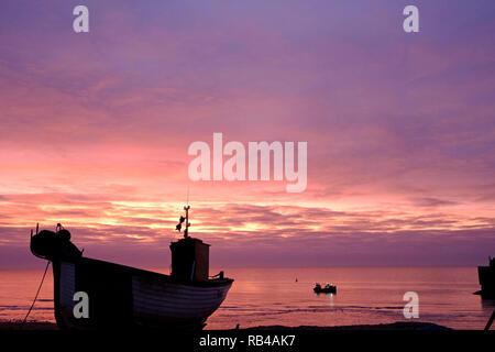 Hastings, East Sussex, UK. 7. Jan 2019. Sehr milden Start in den Tag bei Sonnenaufgang am Strand des Stade Fischer als Fischer ihre Boote laden. Hastings hat den größten Strand Fischereiflotten in Großbritannien gestartet. - Stockfoto