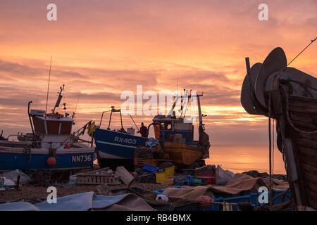 Hastings East Sussex UK. Sehr milden Start in den Tag bei Sonnenaufgang auf dem Stade Fishermens Strand als Fischer ihre Boote laden. Hastings hat den größten Strand-Flotten in Europa. - Stockfoto