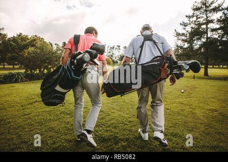 Ansicht der Rückseite zwei älteren Golf Spieler zusammen zu Fuß in den Golfkurs mit Ihrem Golf Taschen. Ältere Golfspieler zu Fuß aus dem Kurs nach dem Spiel - Stockfoto