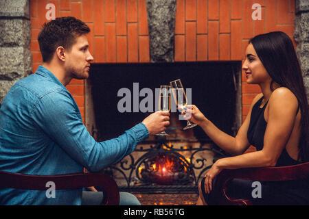 Junger Mann und Frau dating. Sie sitzen in Stühlen und jubeln mit Champagner Gläser. Die Leute schauen sich an. Sie lächelt. - Stockfoto