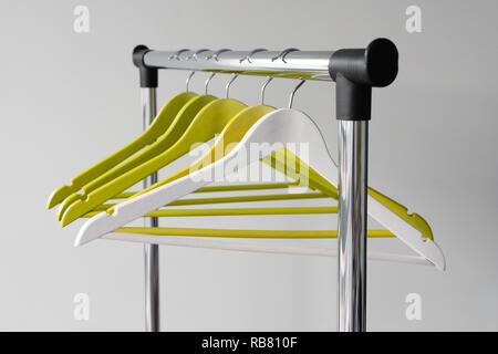Leere Kleiderbügel auf Metallschiene gegen grauen Hintergrund. Rechteckige metall Kleiderstange mit leeren Farbe Holz Kleiderbügel. - Stockfoto