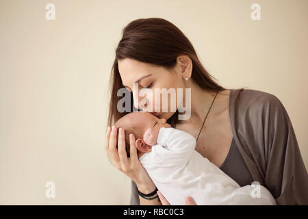 Mutter küssen Neugeborenes Baby auf grauen Hintergrund. Portrait von Frau und Baby - Stockfoto