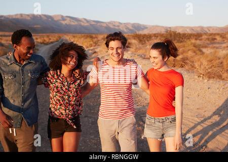 Vier junge erwachsene Freunde lachen auf einer einsamen Straße, in der Nähe - Stockfoto