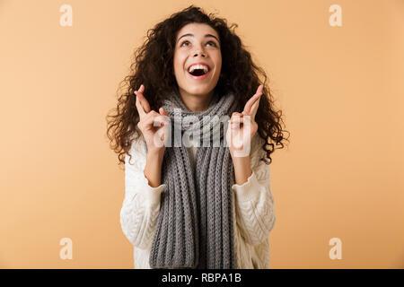 Fröhliche junge Frau tragen winter Schal stehend über beigen Hintergrund isoliert, die erntehaltefinger für gutes Glück gekreuzt - Stockfoto