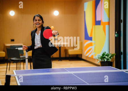 Eine junge indische asiatische Frau in einem Anzug lächelt und lacht, während Sie ping pong in Ihrer startup Office spielt. Sie hat viel Spaß mit einem Kollegen. - Stockfoto