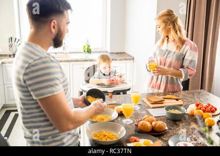 Junge Familie beim Frühstück mit Baby - Stockfoto