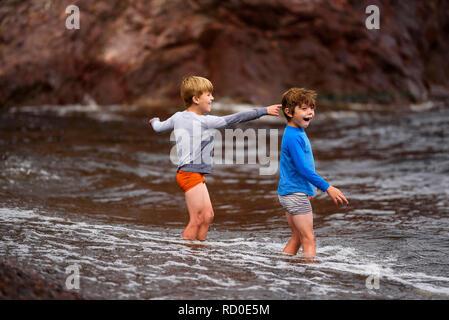 Zwei Jungen stehen Knie tief im Meer Spaß, United States - Stockfoto