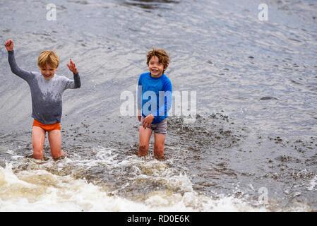 Zwei Jungen stehen Knie tief im Meer, United States - Stockfoto
