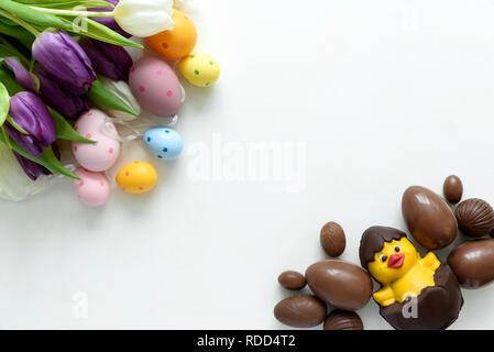 Tulpen, Schokolade Ostereier und Ente auf weißem Holz- Hintergrund. Flach. Ansicht von oben. - Stockfoto