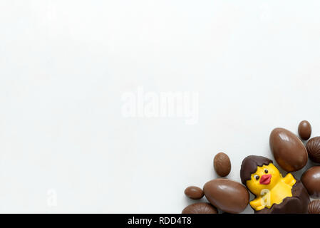Schokolade Ostereier und Ente auf weißem Holz- Hintergrund. Flach. Ansicht von oben. - Stockfoto