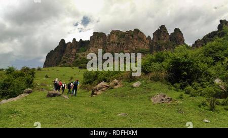 Freudige Reisende ist Spaß beim Wandern entlang der grünen Bergwiese auf dem Hintergrund der bewölkten Himmel. Gruppe der Wanderer zu Fuß auf den Felsen. - Stockfoto