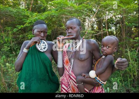 Zwei Surma Frauen mit riesigen Abgerundeten Lippe Platten und halten ein Baby, Kibish, Omo Valley Tal, Äthiopien, Afrika - Stockfoto