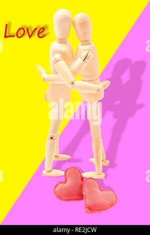 paar in Liebe mit zwei Herzen zu Ihren Füßen umarmen - Stockfoto