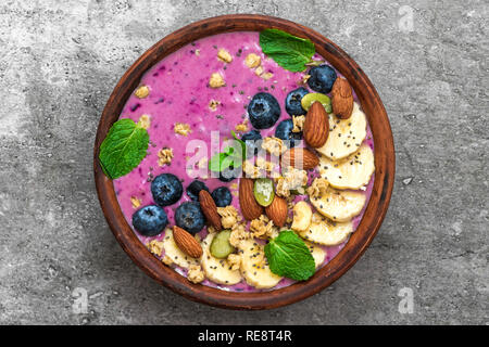 Acai smoothie Schüssel gefüllt mit Banane, Chia und Kürbiskerne, Blaubeere, Mandeln und Müsli. gesund vegan Frühstück. top View - Stockfoto