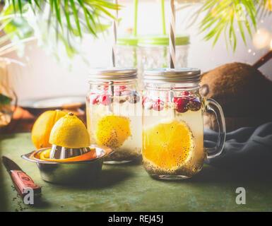 Detox Chia Samen Drink mit orange Obst schneiden, Zitronensaft und Preiselbeeren im Glas Gläser mit Trinkhalm am Küchentisch mit Zutaten. Summ - Stockfoto