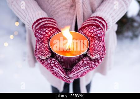 Selektiver Fokus auf Frau gestrickte Handschuhe und Pullover Holding leuchtet eine Kerze im Freien (auch als pitch Taschenlampe oder einen Garten Kerze bekannt), im Freien, in w - Stockfoto