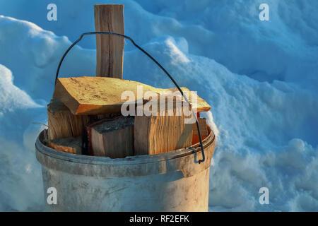 Die Schaufel ist mit Baumstämmen gefüllt. Vorbereitung für die Heizperiode im Winter. In der Nähe der natürlichen Kraftstoff auf Schnee Hintergrund - Stockfoto