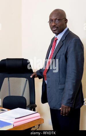 Unternehmer stehen und seinen Stuhl Holding in seinem Büro. - Stockfoto