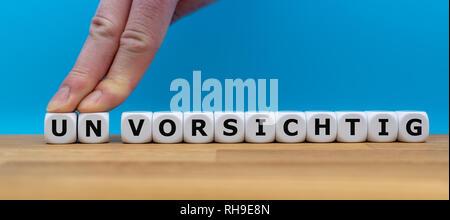 """Würfel Form das deutsche Wort """"UNVORSICHTIG"""" """"vorsichtig"""" (in englischer Sprache), während zwei Finger die Buchstaben """"UN"""" entfernt, um das Wort ändern in 'VORSICHT - Stockfoto"""