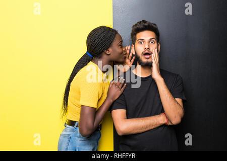 Junge Mixed Race Paar, afrikanische Frau whispering Geheimnisse indischer Mann stand auf verschiedenen gelben und schwarzen Hintergrund - Stockfoto