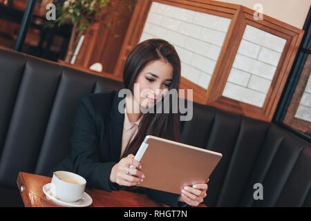 Schöne charmante brunette lächelnden Asiatin mit Tablet am Tisch im Cafe, Studenten, Freiberufler oder junge Manager - Stockfoto