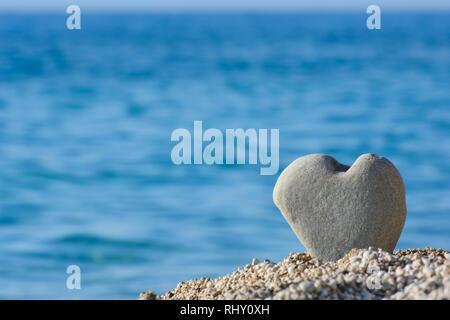Große, graue Herzen shapped Stein in Kiesel am Strand gegen verwackelte Meer und Himmel Hintergrund, gut als Kopie Raum - Stockfoto