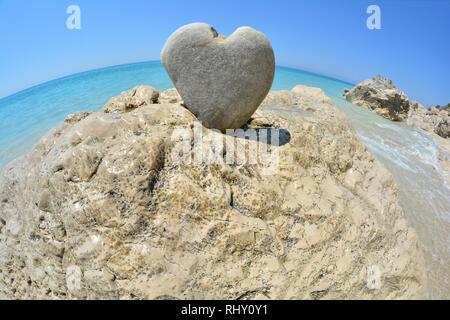 Herzförmige Stein auf großen, weißen Felsen und türkisem Wasser und blauer Himmel im Hintergrund, Fisheye Landschaft, Lefkada, Griechenland - Stockfoto