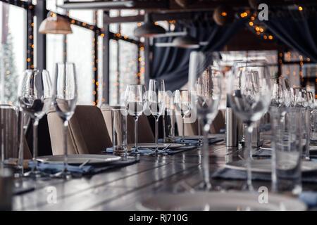Restaurant, Glas Wein und Wasser Gläser, Teller, Spice, Gabeln und Messer auf Textil Servietten stehen in einer Reihe auf einem grauen Holztisch. Anhand von quantitativen Simulatio - Stockfoto
