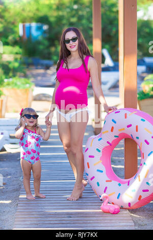 Schwangere Frau am Strand gesunden Urlaub mit niedlichen Baby Tochter tragen rosa stilvolle Schwimmen tragen posieren. Familie Liebe Szene der schönen Dame und Fu - Stockfoto