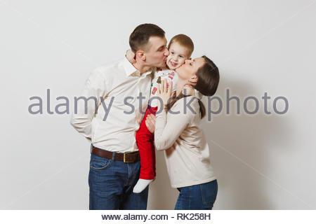 Fröhlich lächelnden jungen Mann, Frau, küssen, umarmen kleinen niedlichen Kind Junge auf weißem Hintergrund. Vater, Mutter, Kind, der Sohn. Parentho - Stockfoto