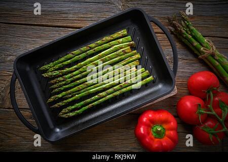 Spargel vom Grill auf Gusseisen Grillpfanne auf Holz Tisch mit Tomaten und Paprika. - Stockfoto