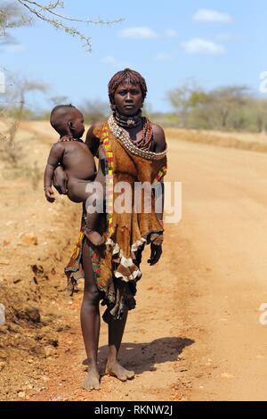 Frau aus Hamar Stamm, mit ihrem Baby Junge am Straßenrand, Äthiopien, Ostafrika. - Stockfoto