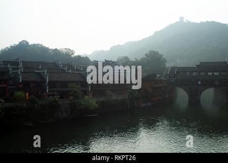 """Die frühen Morgennebel des Triebwerks eine alte Steinbrücke in Fenghuang. Was bedeutet """"Phoenix"""" auf Chinesisch, Fenghuang wurde nach dem mythischen Vogel, der im-Namens - Stockfoto"""