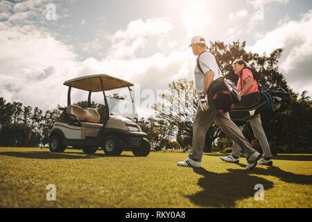 Ältere Golfspieler zusammen wandern in den Golf mit ihren Golftaschen. Ältere Golfspieler zu sprechen und nach dem Spiel. - Stockfoto
