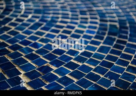 Kleine blaue Mosaikfliesen in einem kreisförmigen Muster - Stockfoto