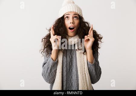 Fröhliche junge Frau tragen winter Schal auf weißem Hintergrund, halten die Daumen für gutes Glück gekreuzt - Stockfoto
