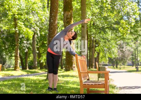 Erwachsene Frau tragen Sportswear dehnen in Park an einem sonnigen Tag - Stockfoto