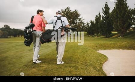Ansicht der Rückseite zwei älteren Golf Spieler zusammen zu Fuß in den Golfkurs mit Ihrem Golf Taschen. Ältere Golfspieler auf dem Weg zur nächsten Bohrung. - Stockfoto