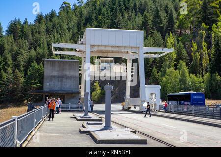 Touristen verlassen ihre Tour Bus an der Oberseite der Benmore Damm zu gehen und Fotos der Ansicht unten in Neuseeland nehmen - Stockfoto