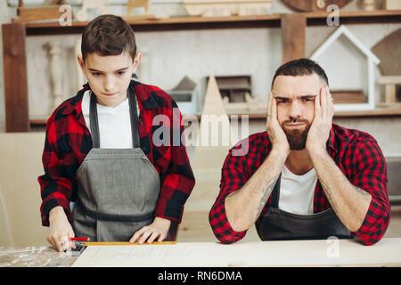 Stressvolle missfallen Vater und seinem Kind Junge engagieren in WOODWORKER Klassen, sitzen an Workshop mit Hände auf den Kopf und verwirrte Gesichter, als wenn Sie sich n - Stockfoto