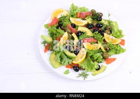 Salat mit Lachs, Avocado und Oliven auf weißem Hintergrund - Stockfoto
