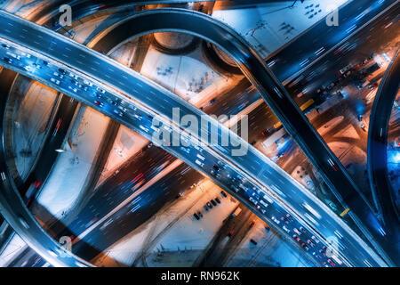 Luftaufnahme der Weg in die moderne Stadt in der Nacht im Winter. Blick von oben auf den Verkehr in Highway Kreuzung mit Stadt Ausleuchtung. Autos auf Elevated Road. Inte - Stockfoto