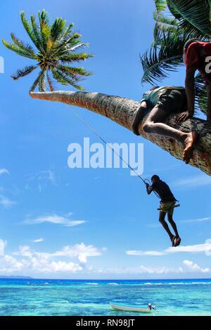 Einheimische Kinder schwingen an einem Seil schwingen in Lavena Dorf, Insel Taveuni, Fidschi. Taveuni ist die drittgrößte Insel in Fidschi. - Stockfoto