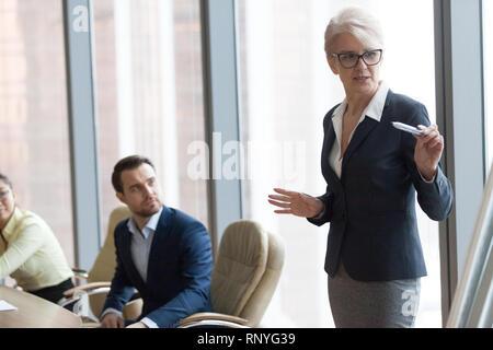 Zuversichtlich im mittleren Alter Mentor sprechen Sie eine Präsentation halten an Executive Team Training - Stockfoto