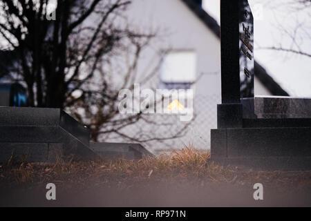 Menorah bokeh Silhouette in das Fenster eines Hauses in der Nähe der Vandalismus Gräber mit NS-Symbolen in blau Spray - auf den beschädigten Gräber - Jüdischer Friedhof in Quatzenheim in der Nähe von Straßburg gestrichen. - Stockfoto