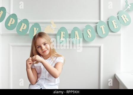 Süße kleine blonde Mädchen sitzt in einem hellen Raum in der Nähe der Fenster auf dem Hintergrund der Streamer mit den Worten Frohe Ostern Holding eine Herzform. - Stockfoto