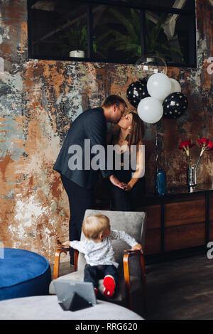 Eltern küssen, Sohn sitzt auf einem Stuhl und zurück an. - Stockfoto